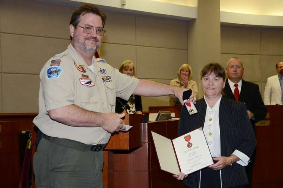 Paul Cowan, Boy Scouts of America Representative, presents a National Honor Medal to Truitt MS teacher Christine Allen-Jackson during the Board of Trustees meeting on Thursday, June 20.