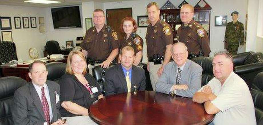 Attending the signing ceremonies were, seated, from left, Major Thomas Goodfellow, Inspector Crystal Irvin, Sheriff Troy E. Nehls, Precinct 3 Commissioner Andy Meyers and Inspector George Johnson. Standing, from left, Lt. Chris Pressler, Sgt. Angel Rader, Captain Jule Brownfield and Lt. Daniel Quam.