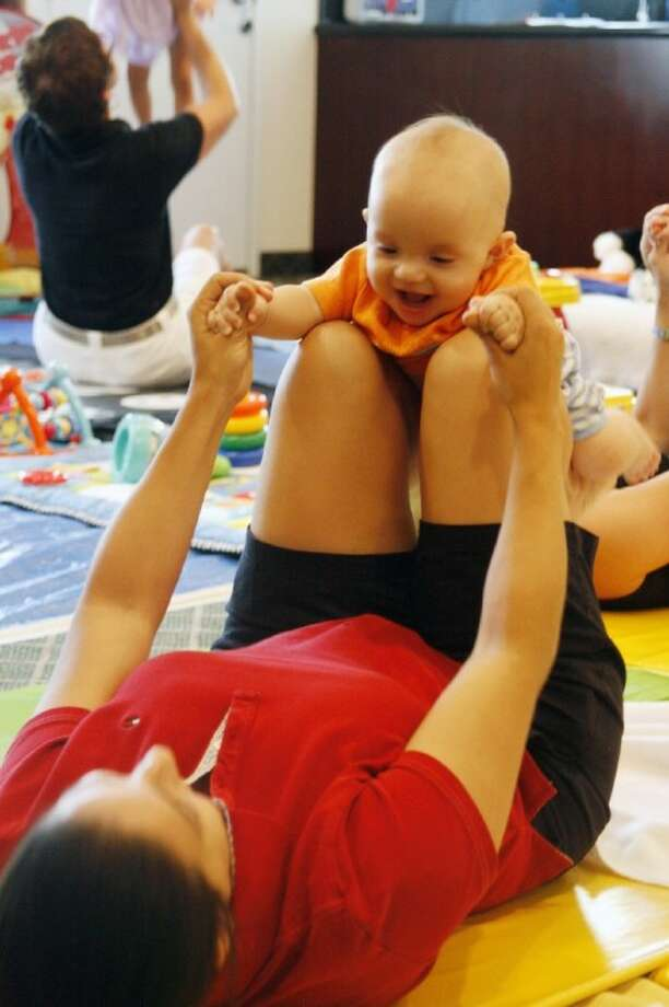 "A mom and her baby participate in the ""flying"" exercise, which stimulates babies' sensory experiences, during the Baby Sensory program which meets in the Humble area."