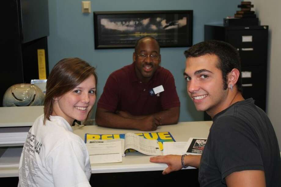 LSC-Tomball employee Durell Forte assists two students enroll in courses. Photo: Submitted