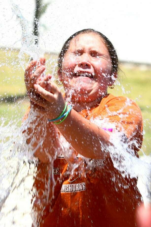 Olivia Clarke, 9, catches a water balloon during a team-building exercise Wednesday at Camp Invention at Magnolia West High School.