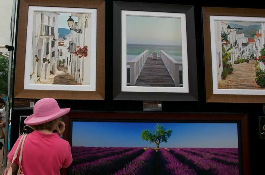 A woman gets a closer look at fine art photography prints during a previous The Woodlands Waterway Arts Festival in The Woodlands. This year's festival is set for April 12-13. Photo: Staff Photo By Eric S. Swist