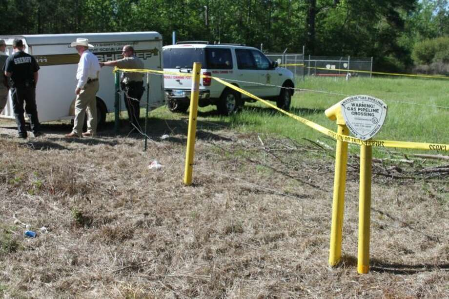 Crime scene tape stretches along a property on CR 332 where law enforcement officers are looking for more human remains after a skull and portions of vertebrae were found Thursday evening, April 11, by two citizens riding four-wheelers along a pipeline easement. Photo: VANESA BRASHIER