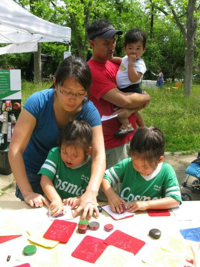 Kids and their parents who attend Spring Fling at the Nature Discovery Center enjoy working together on nature crafts like leaf rubbings.