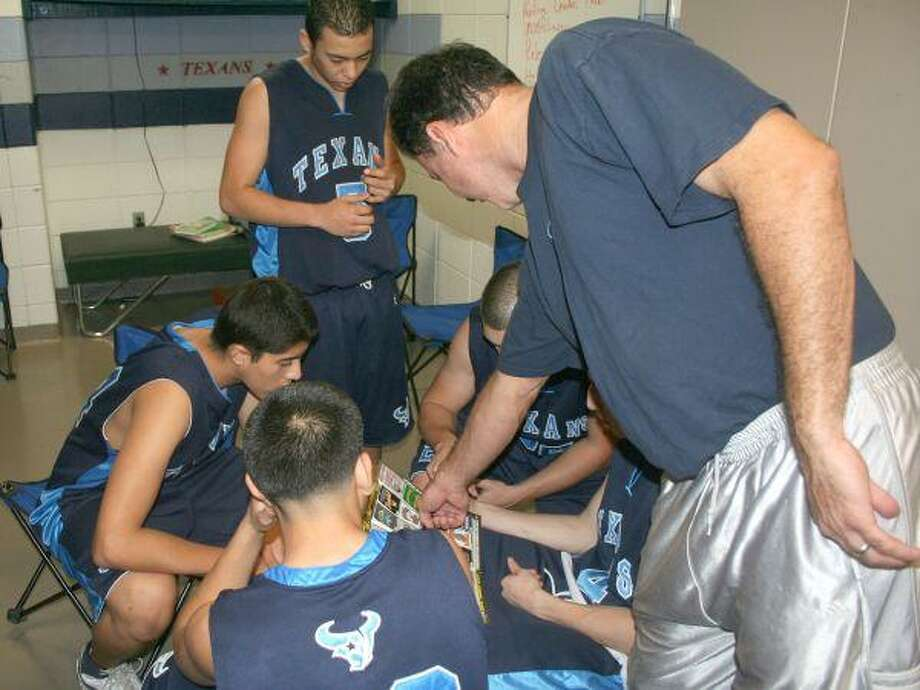 Sam Rayburn head basketball coach Jorge Negron, shown helping one of his teams pick out a T-shirt design, is stepping down to take the head coach's job at Lamar Consolidated ISD's new high school.