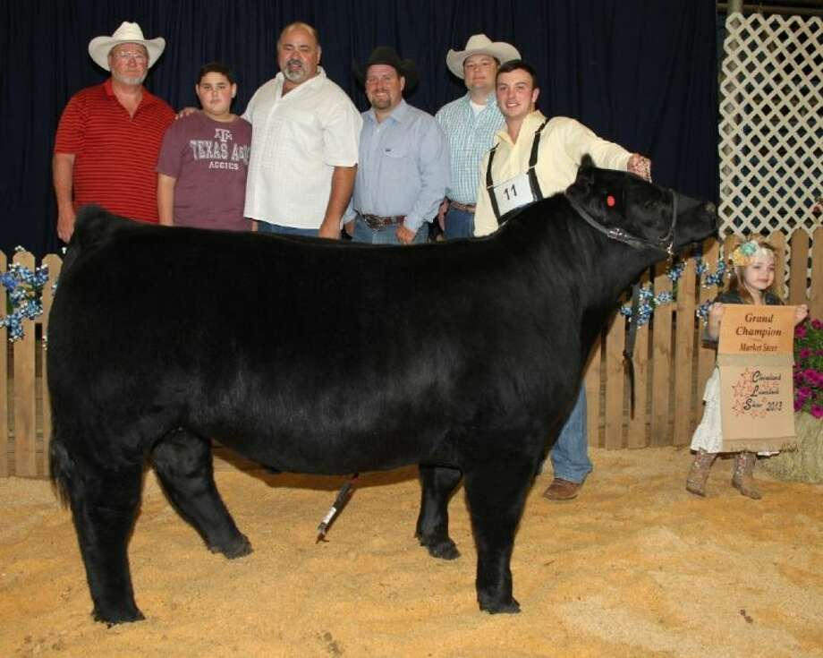 "Ethan Worthy of Liberty FFA sold his Grand Champion Steer for $8,500 to Bryan Neal and Steve Primeaux, owners of Tricare Hospice, and Chance Ward, at the 2013 Youth Auction Sale on Friday, April 12. The auction is part of the Cleveland Livestock Show. Neal later said that he and his business partners purchased the steer and other auction entries ""because they believe in the community."" Photo: VANESA BRASHIER"