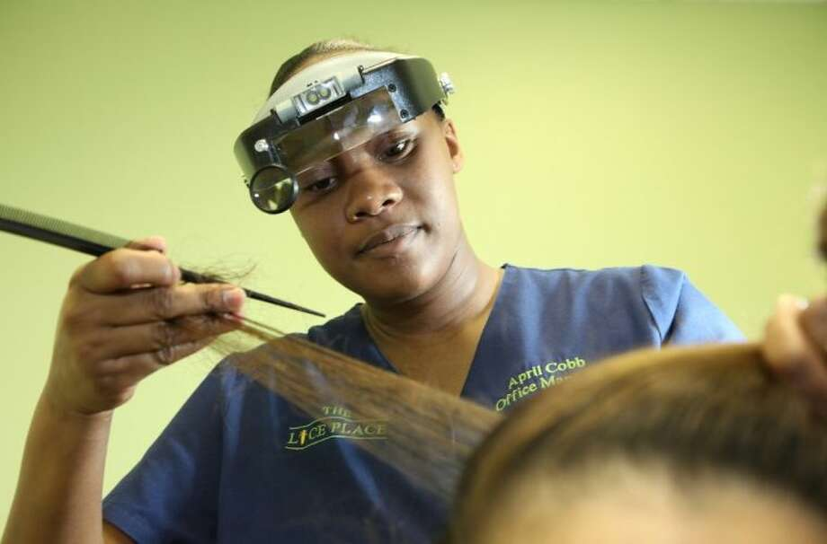 April Cobb does a visual inspection for lice at The Lice Place in Katy. Photo: Photo By Alan Warren