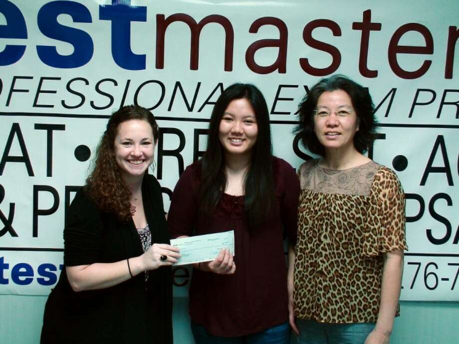 Clear Lake High School junior Joan Zhang, center, is handed a $1,000 check by Testmasters employee Jessie Weber. Zhang's mother, Wei Han,is on the right.