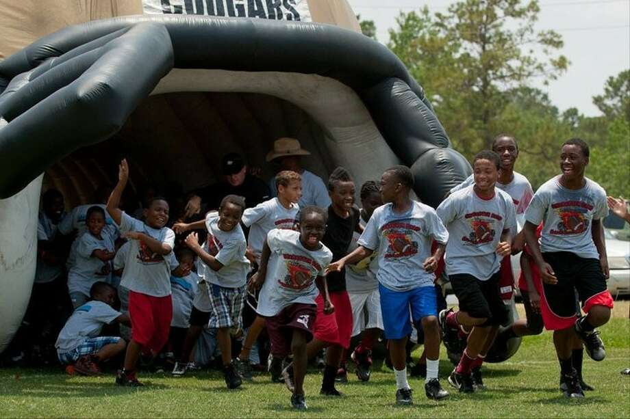 Members of the Fort Bend Falcons youth football team run through Northland Christian's helmet during the Arms of Hope football camp on June 11.