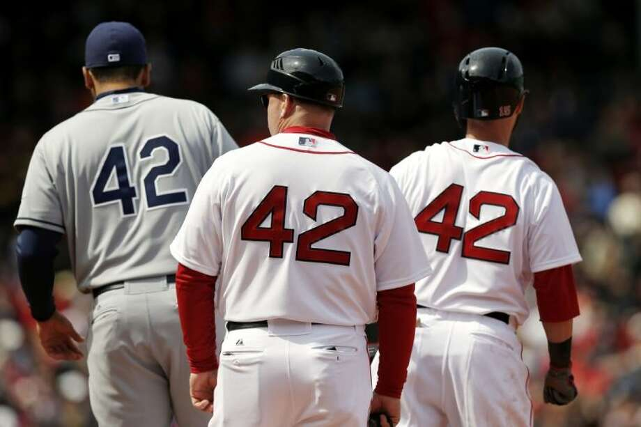 Tampa Bay Rays first baseman James Loney, left, Boston Red Sox's Dustin Pedroia (middle) and Red Sox first base coach Arnie Beyeler survey the scene on Jackie Robinson Day at Fenway Park. All players and coaches wore Robinson's No. 42 on Monday.