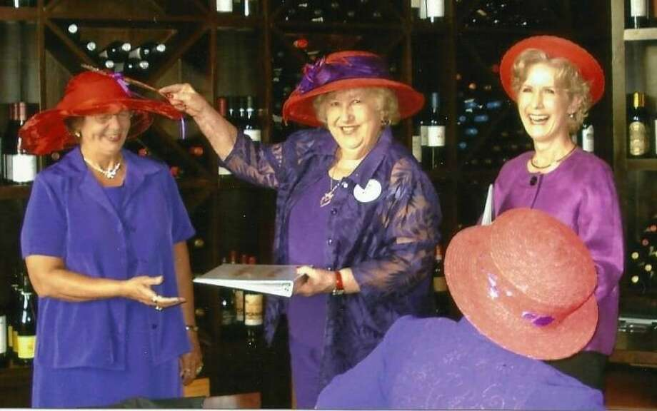 Queen Mari Rich (Queen Da-Dee) anoints Joan Pate as Duchess of Divots and Carolyn Jamail as Lady Luck as she presents each a handbook that tells all about The Red Hat Society. Such a ceremony is held at the incoming of each new member. Photo: Submitted Photo