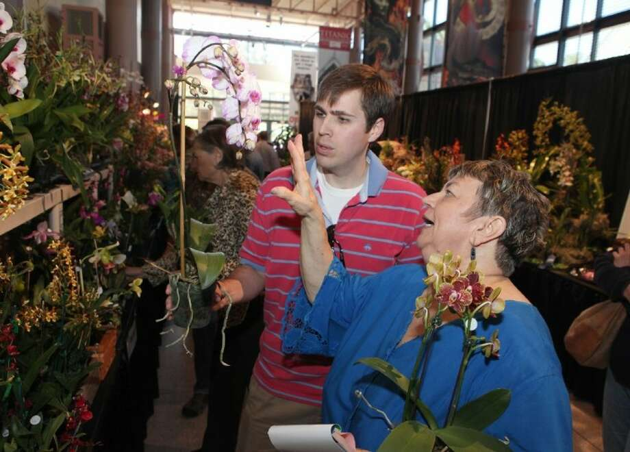 Matthew McIntyre of Houston gets advice from Terri Palmer of Orchid Plus before he buys an orchid at the Orchid Show and Sale at the Houston Museum of Natural Science on Saturday.