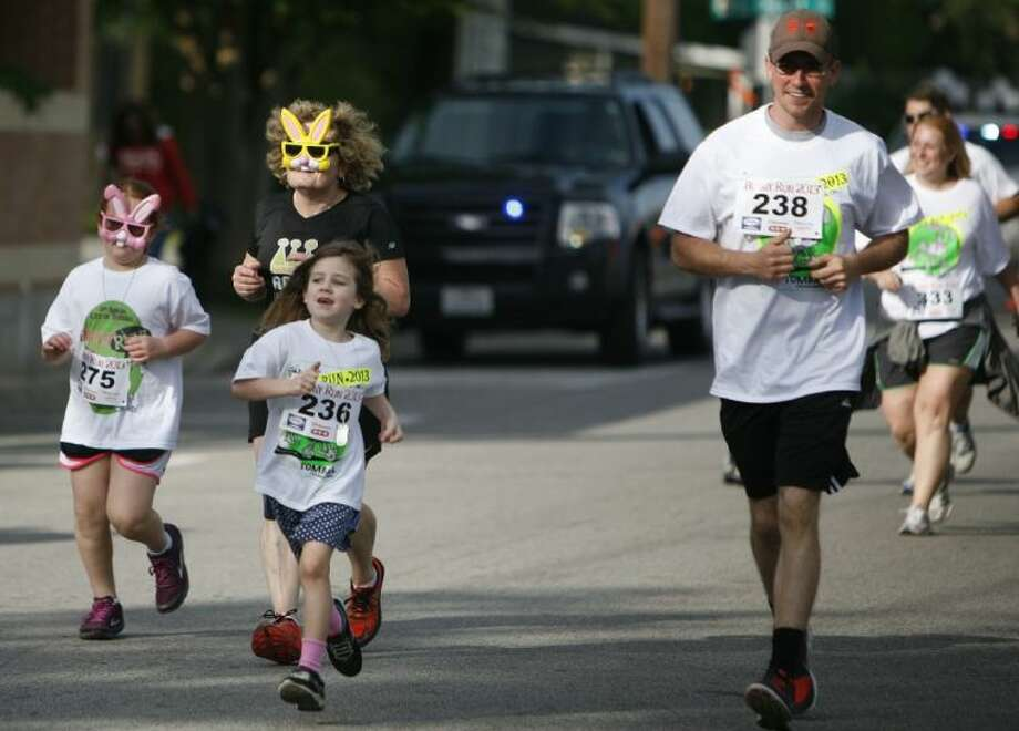 A family make a run for the finish line during Saturday's 5th annual Tomball Bunny Run in downtown Tomball. A record number of runners participated in the event this year. Photo: Staff Photo By Eric Swist