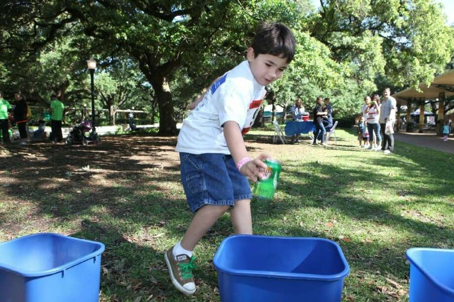 Tyler Robertson, 8, of Houston, competes in a recycling race as part of Earth Day at the Houston Zoo Saturday. Photo: ALAN WARREN