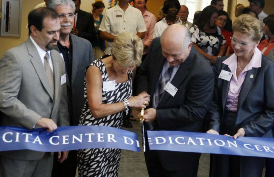 Lone Star College System board of trustees member Stephanie Marquard, center, cuts the ribbon with LSCS Chancellor Dr. Richard Carpenter during the new LSC-Atascocita Center dedication ceremony June 14.