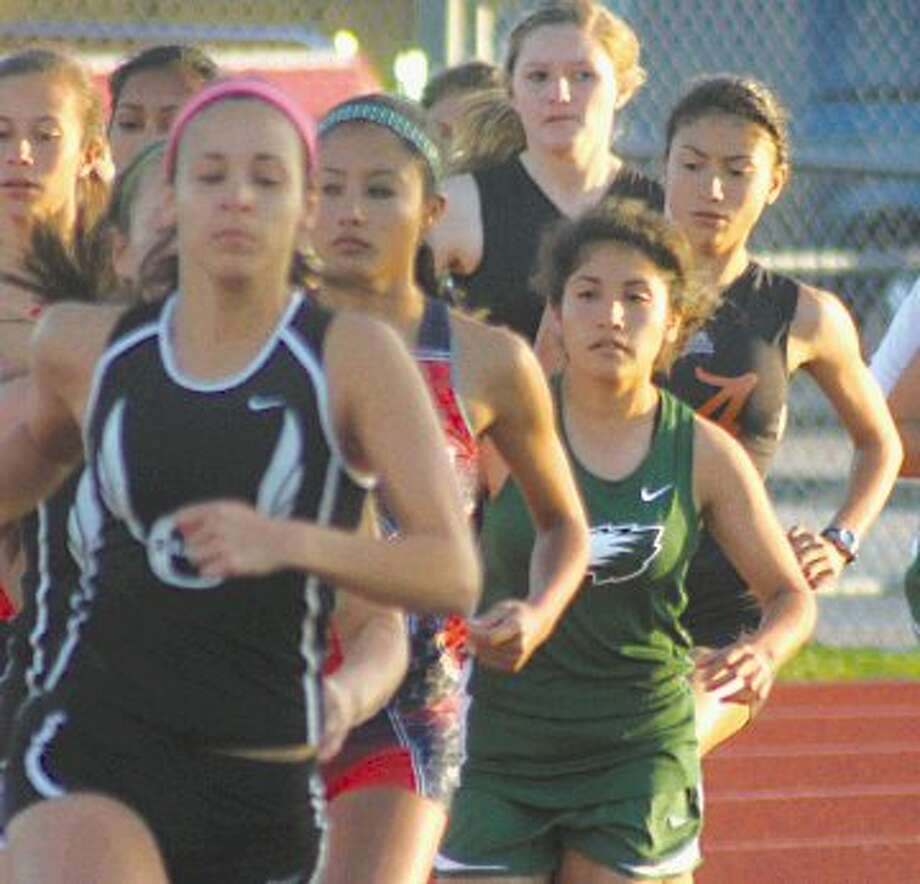 Pasadena's Emely Morgado (green jersey) finds herself pinched against the inside curve as the large pack navigates the opening turn to the 1600-meter race on the final night of the 22-5A varsity track and field meet. But Morgado went on to win the district championship in dramatic fashion. She advances to the Area meet this week.