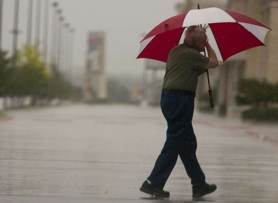A work-bound man braves the rain with his trusty umbrella on Tuesday morning.