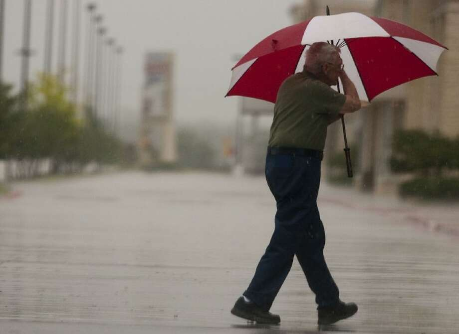 A work-bound man braves the rain with his trusty umbrella Tuesday morning. Photo: Patric Schneider/The Examiner