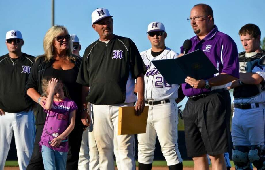 Flanked by his players and assistant coaches and accompanied by his family, Humble baseball coach David Sitton listens to his brother, Humble ISD trustee Robert Sitton, read a declaration from U.S. Congressman Ted Poe during a ceremony honoring the coach's 500th victory before the Wildcats' game against Huntsville April 18. Photo: Stephen Whitfield