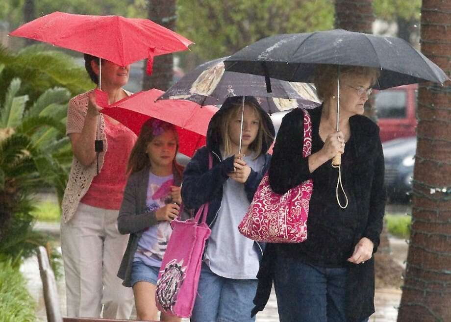 Jeanne Lachke (front) and Dorothy Petru (back) brave the rain to take their granddaughters Abbey, 8, (second from front) and Katie Petru, 7, to lunch.