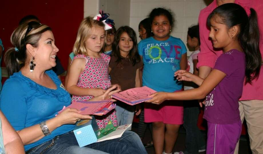 """Jocelyn Ortis, a student in Delphine Cruz's first-grade class, presents a """"Thank You"""" card collectively to volunteers at Stephen F. Austin Elementary School on April 18 during the Dayton Independent School District's Volunteer Appreciation Week. Volunteer Amanda Cortina accepts a card from each class after each group either read its own poem or sang its own lyrics to familiar melodies. Photo: STEPHEN THOMAS"""