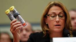 Mylan CEO Heather Bresch holds up an EpiPen while testifying on Capitol Hill on Sept. 21. Republicans and Democrats criticized her for being vague about the company's finances and profits.