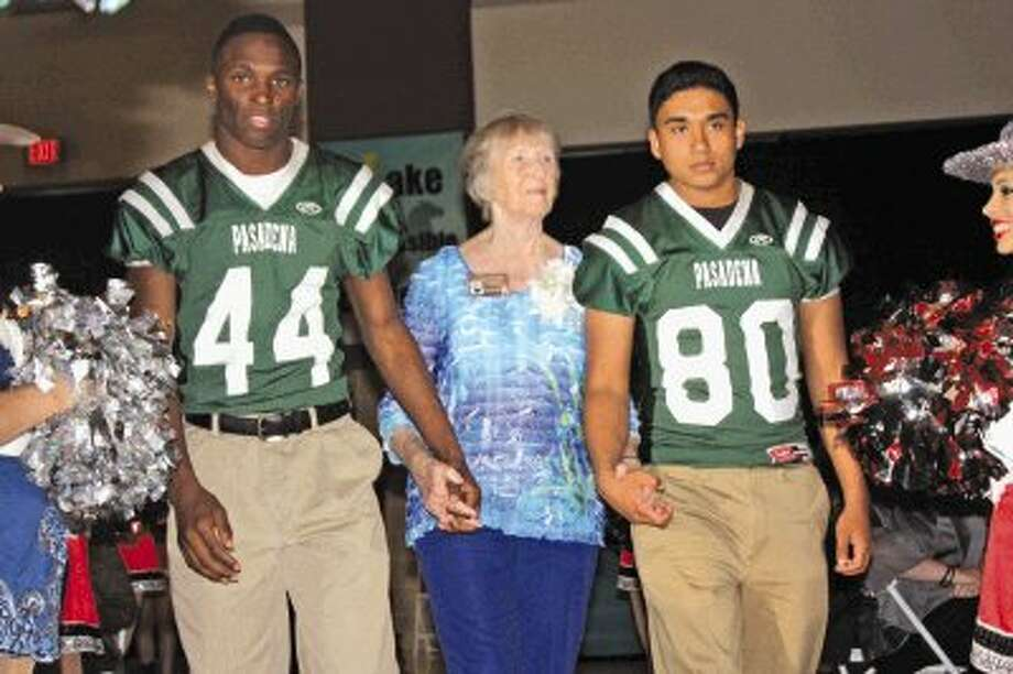 Milly Spencer, widow of Pasadena High School football star Mickey Spencer from the 1940s, is escorted down the red carpet by two current Eagles during Saturday night's Pasadena ISD Athletics Hall of Fame. Mickey was the first football player to capture All-State honors for his play in 1946 when Pasadena won the District 14-2A crown, the first year the Eagles competed as a 2A school. Photo: Photo By Robert Avery