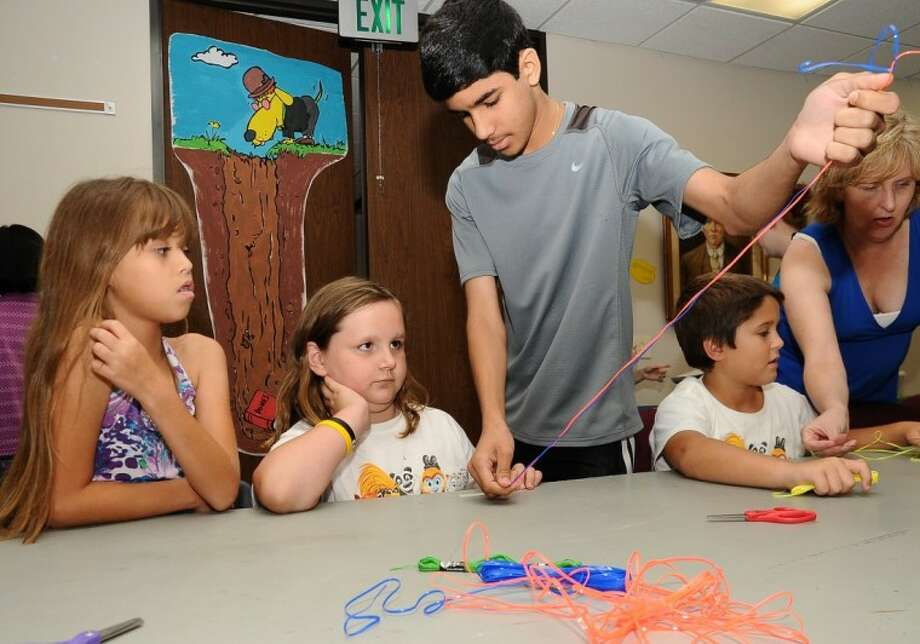 Volunteer Karan Jerath shows, left to right, Elizabeth Ricaldi and Abby Riley how to make friendship bracelets during a craft program at Friendswood Public Library Wednesday, 6/22.