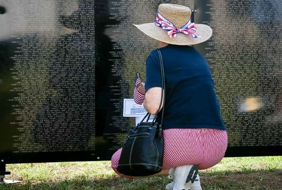 Submitted photoA Sugar Land resident reads names on the Wall That Heals when it visited Sugar Land's Memorial Park in 2010.