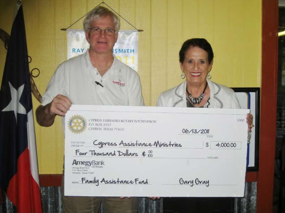 Gary Gray, president of the Rotary Club of Cypress-Fairbanks presents Joan Christiansen, executive director of Cypress Assistance Ministries, with the donation. (submitted photo)