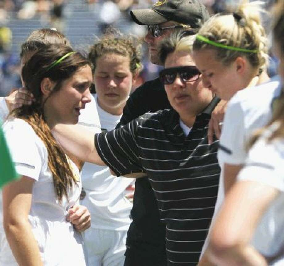 Klein Oak coach Becky Cobb comforts her players last Thursday afternoon after Plano West topped the Lady Panthers 2-0 in the Class 5A state semifinals at Birkelbach Field in Georgetown. Photo: Jason Fochtman / Houston Community Newspapers
