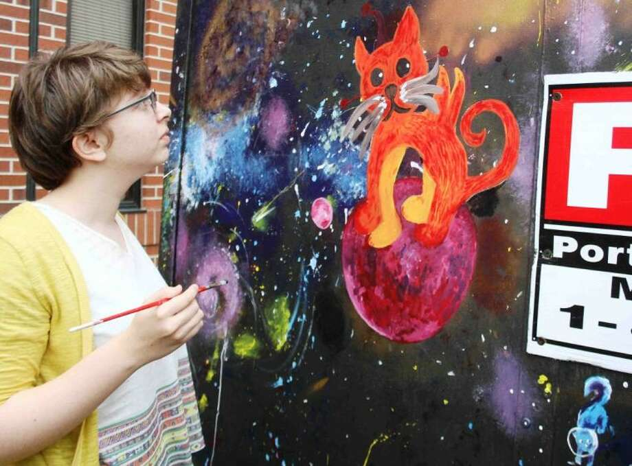 TWHS sophomore Alyssa Drew puts the final touches on a kitten in space for this weekend's arts festival along The Woodlands Waterway.