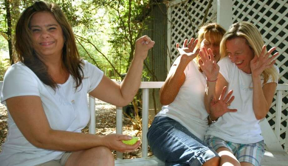Debra Hoyt (left) enjoys the reaction of friends and partners Bea Gutierrez and Reyne Haines after flicking flour at them. Photo: Rusty Graham