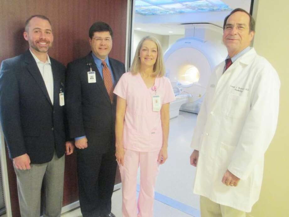 "Pictured outside the room housing the ""breast coil"" in most powerful scanner in the area are (from left) Matt Evans, director of outpatient imaging; Louis Smith, Memorial Hermann Northeast Hospital CEO, Elizabeth Dukes, RDMS, lead mammography technician for the Breast Center; and Louis Bujnoch, M.D., medical director for the Memorial Hermann Northeast Breast Center. The scanner now includes an attachment which allows Memorial Hermann Northeast to perform breast MRIs."