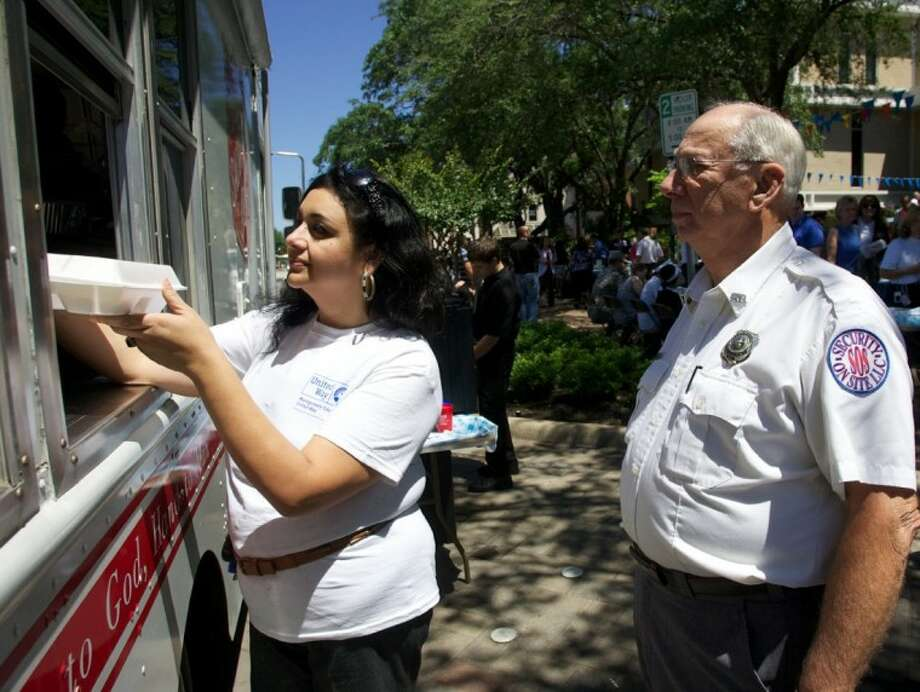 A United Way volunteer collects a barbecue lunch as courthouse employee Robert Steward waits in line during Montgomery County United Way's third annual Volunteer Appreciation Celebration April 18 at the Montgomery County Courthouse in Conroe. Photo: Staff Photo By Eric S. Swist