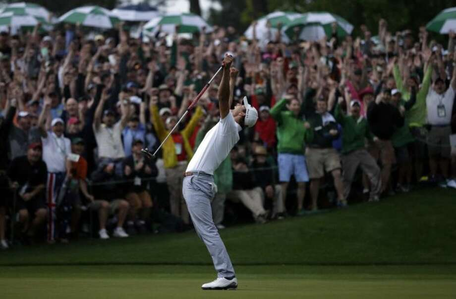 Adam Scott, of Australia, celebrates after making a birdie putt on the second playoff hole to win the Masters golf tournament.