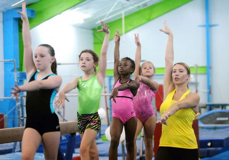 """Three time Olympic gold medalist Svetlana Boguinskaia, once called the """"Belrusian Swan"""" works with young gymnasts like, left to right, Madison McInnis, Grace Morley, Analicia Zuniga and Karsyn Foster during annual Olympia Gymnastics Training Camp at MGA Gymanstics, Tuesday, 6/21."""