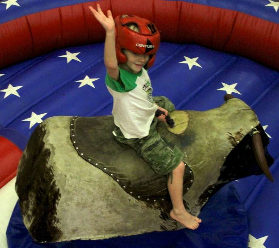 Spencer Bright, age 5, rides a mechanical bull at the Cleveland Civic Center on June 23. The event was part of the Austin Memorial Library's summer reading program. Photo: Jason Fochtman