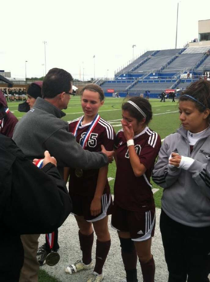 Magnolia Principal Jeff Springer presents state semifinalist bronze medals to Allison Abendschein, left, and Zoe Bauerschmidt after the Lady Bulldogs' 4-2 loss to Denton Guyer in the Class 4A State Tournament on Thursday at Birkelbach Field in Georgetown.