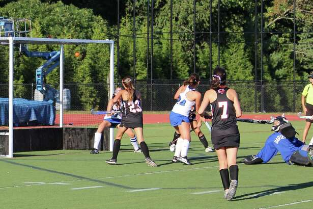 At left, Ellery Baran's shot flies into the net as she follows through at right.