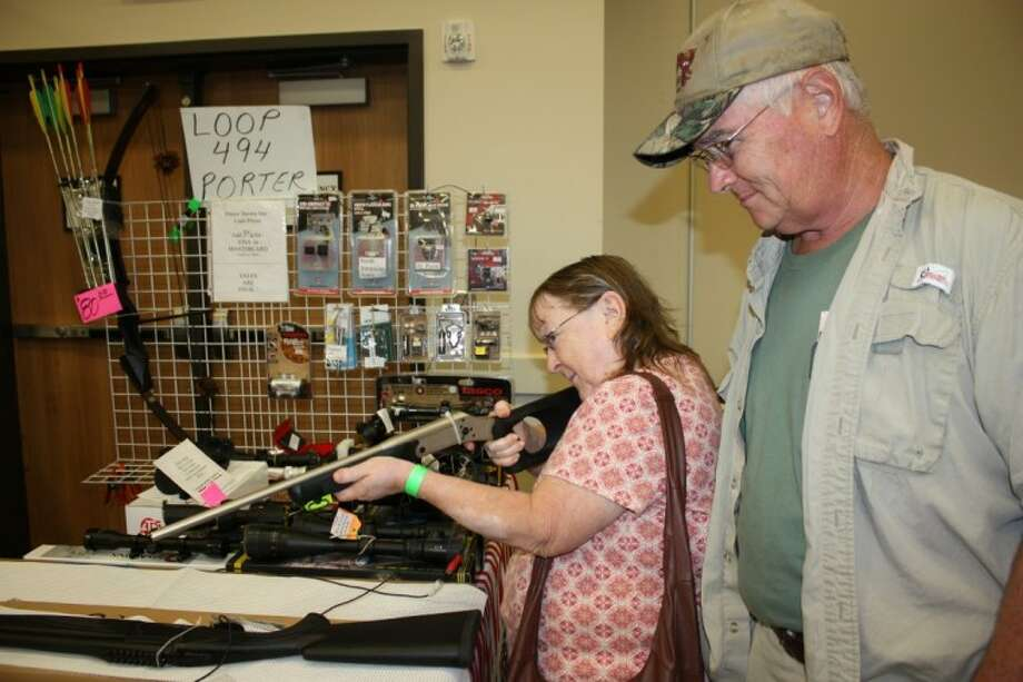 Susan Henley, left, peers down the barrel of the Rossy .410 shotgun while her husband, Tom Henley, right, looks at the prices during the South Texas Knife, Gun and Coin Expo on June 25. The couple said that they were excited to attend the event and hoped that more gun shows are held in Dayton.
