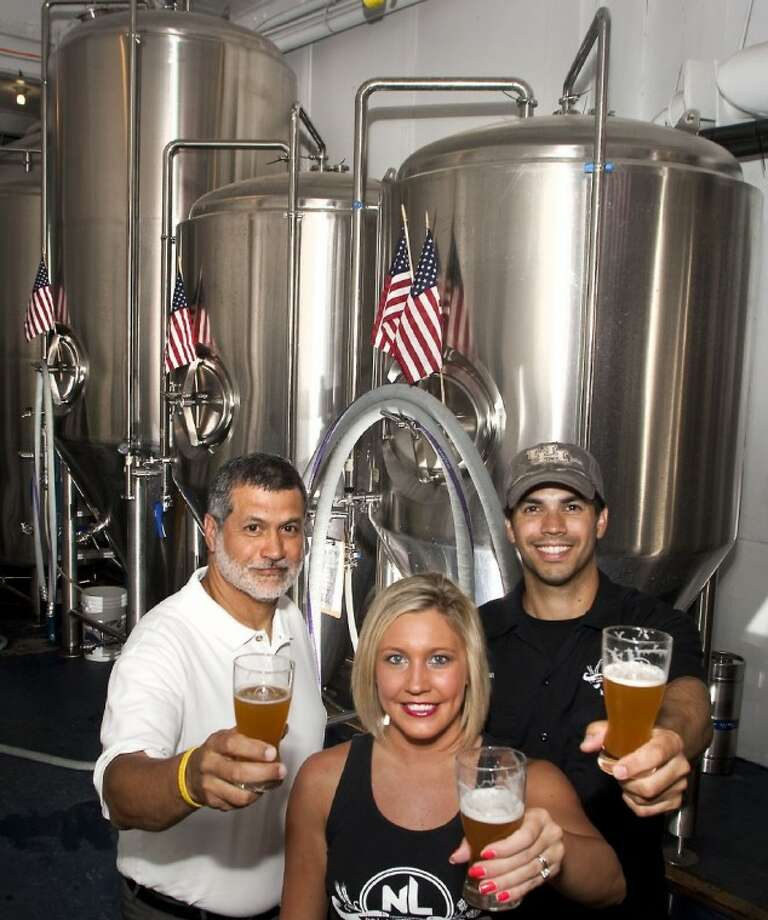 Photo by Patric ScneiderGilberto, Jennifer and Brian Royo, co-owners of No Label Brewing Co., show off freshly brewed pints of the microbrewery's own beer, produced on site in the 15-barrel system.