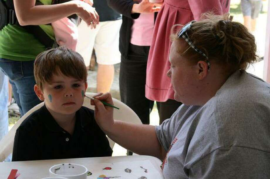 A volunteers paints the face of guest Hayden at the Fight Against Melanoma fundraiser at Bill's Cafe March 28.