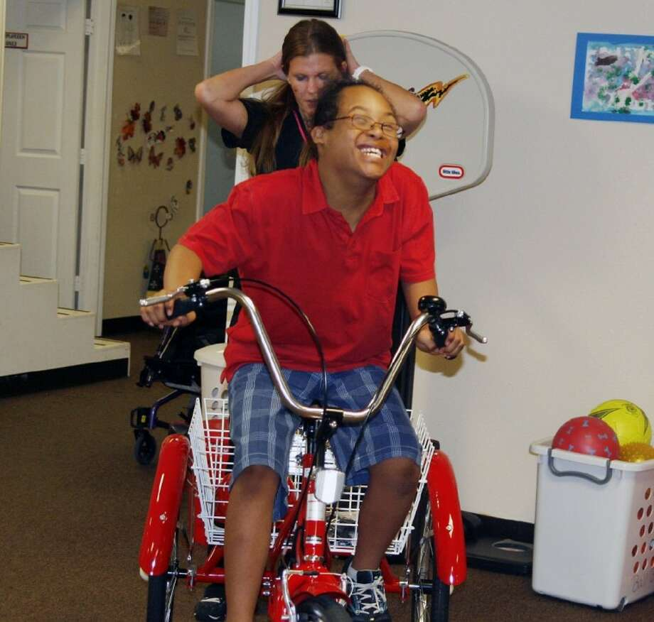 Fall Creek resident Tyger Anderson beams as he rides his new bicycle for the first time at Active Development Therapy in Porter June 23 where he gets therapy.
