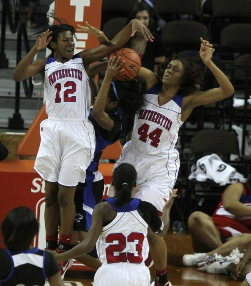 Dekaney guard Jalessa Chapel (25) gets her shot blocked and fouled after being double teamed by Dekaney center Amber Atkins (44) and forward Regine Adams (12) during the Class 5A girls' basketball state championship game at the Frank Erwin Center on March 3 in Austin. Photo: Jason Fochtman