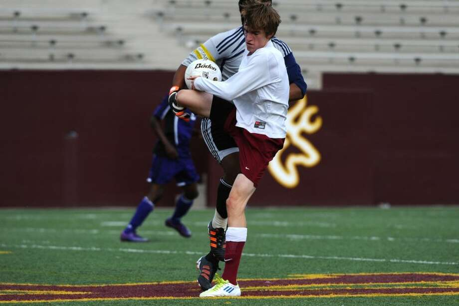 Deer Park's Grant Mobley (3) collides with the Morton Ranch goal keeper in the 2012 Region III playoff game against Clements Friday, 4/13. Photo: KIRK SIDES