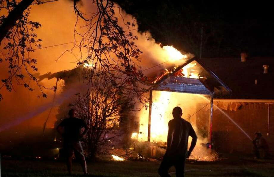A person looks on as emergency workers fight a house fire after a nearby fertilizer plant exploded Wednesday, April 17, 2013, in West, Texas. (AP Photo/ Waco Tribune Herald, Rod Aydelotte) Photo: Rod Aydelotte