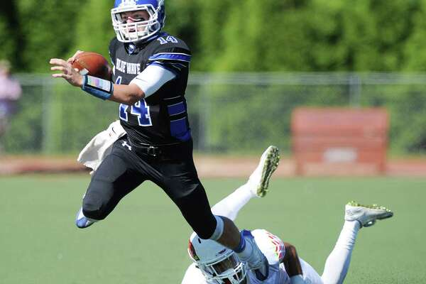 Darien quarterback Brian Peters (#14) escapes the clutches of Jon Aziz (#5) of Greenwich during the high school football game between Greenwich High School and Darien High School at Darien, Conn., Saturday, Sept. 24, 2016. Darien defeated Greenwich 42-35.