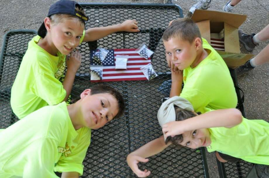 From Tigers to Webelos in rank, Cub Scouts Ethan Cooper, Joshua Derrington, Ethan Ellis, and Austin Merritt finish up the folding of their flags. About 255 pocket-sized flags will be sent to troops, many on the front lines. Photo: SUBMITTED PHOTO