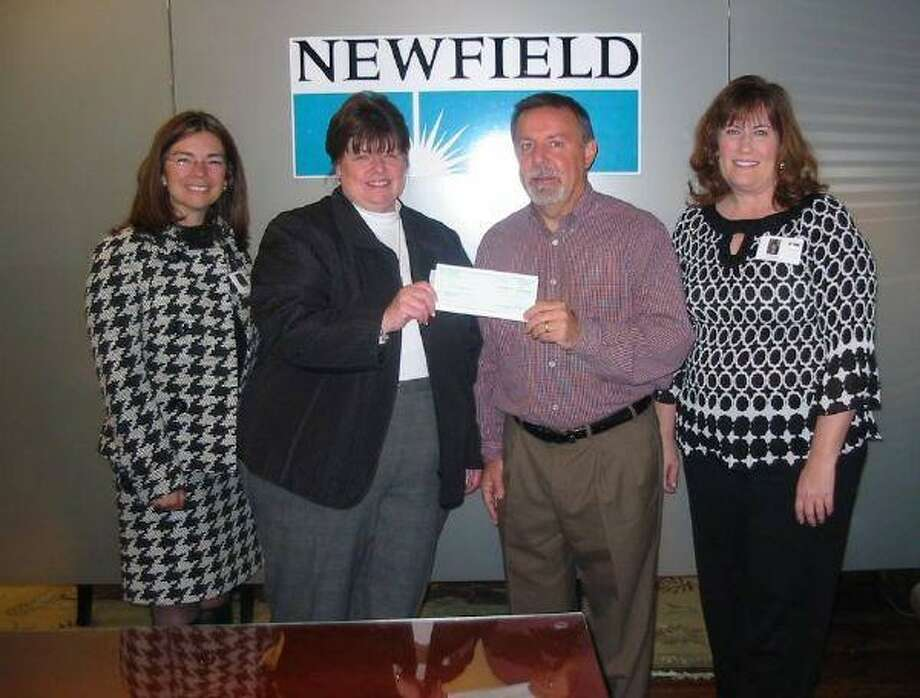 Kim Brusatori, founder and development director of Village Learning & Achievement Center, accepts a check for 5,000 from Newfield Exploration Company employee sponsor John Austin on behalf of the Newfield Foundation. Also pictured are Sheila Turner, far left, major donor coordinator, and Amy McIntee, far right, communications coordinator at VLAC.